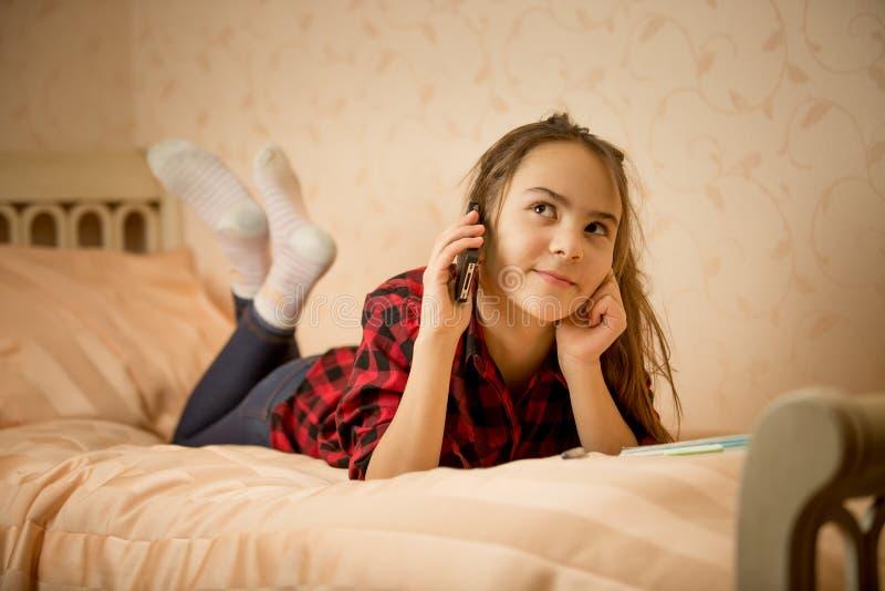 Tonårs- flicka som ligger i sovrum och talar vid telefonen royaltyfria foton