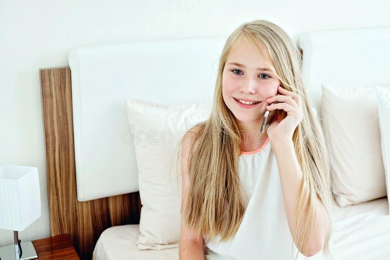 Tonårs- flicka som ligger på säng genom att använda en mobiltelefon royaltyfria foton