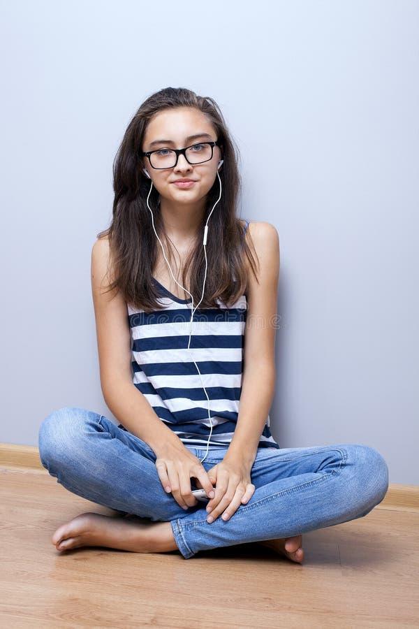 Tonårs- flicka som lyssnar till musik som ser kameran fotografering för bildbyråer