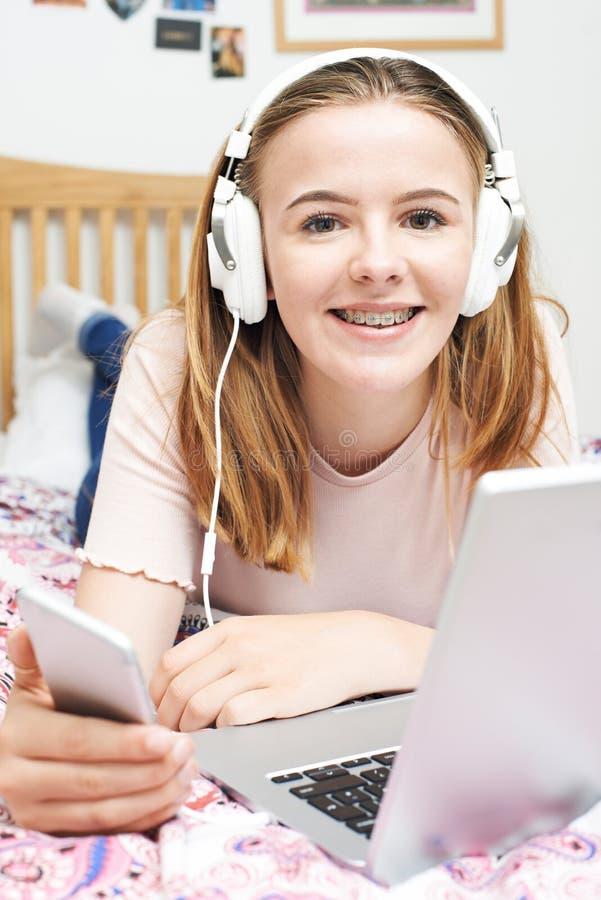 Tonårs- flicka som lyssnar till musikstunden genom att använda mobiltelefonen arkivbilder