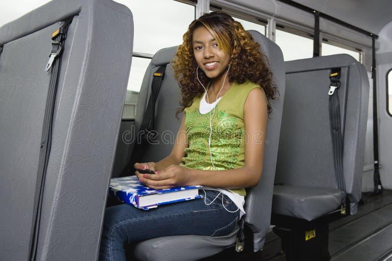Tonårs- flicka som lyssnar till spelaren MP3 på bussen royaltyfri bild