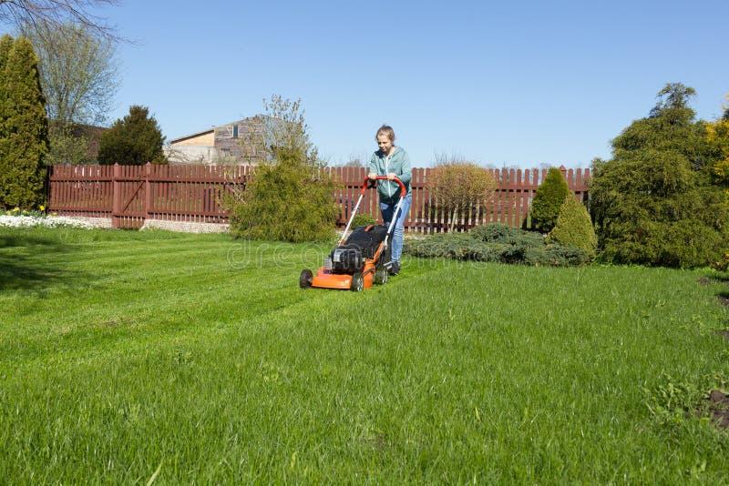 Tonårs- flicka som mejar gräs royaltyfri foto