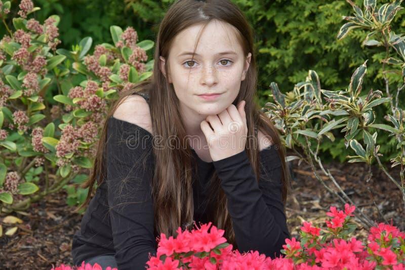 Tonårs- flicka som poserar för foto i trädgården arkivbilder