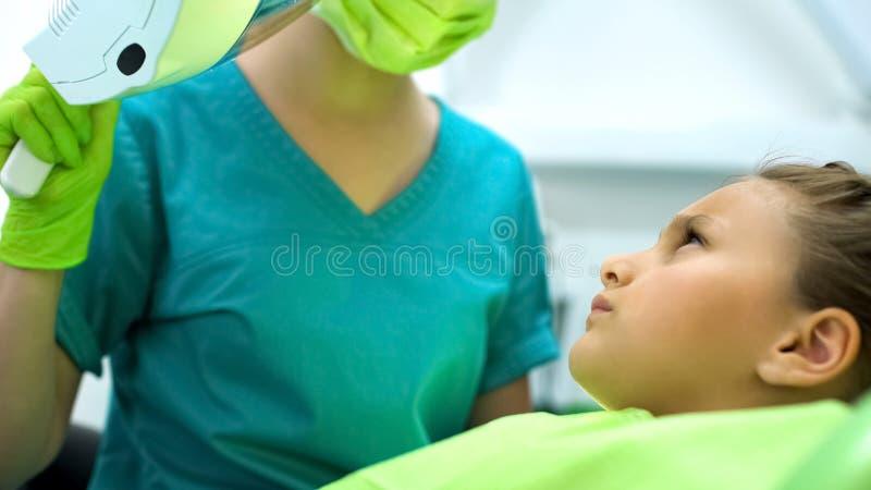 Tonårs- flicka som ser den pediatriska tandläkaren som skrämmas av borrande, kariesborttagning arkivfoto