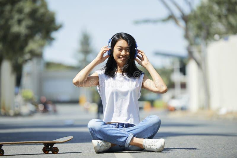 Tonårs- flicka som sitter på vägen royaltyfri fotografi