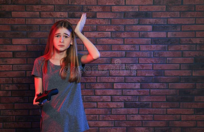 Tonårs- flicka som spelar videospel med kontrollanten nära tegelstenväggen arkivfoto