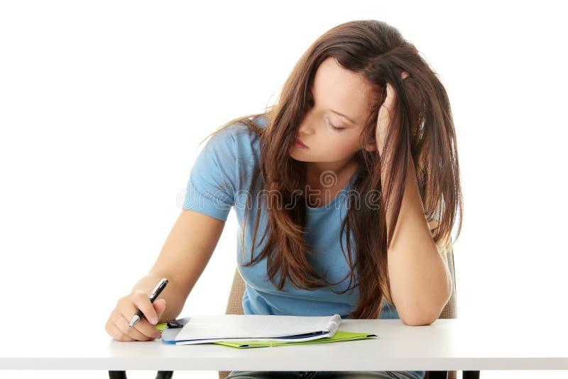 Tonårs- flicka som studerar på skrivbordet som tröttas royaltyfria bilder