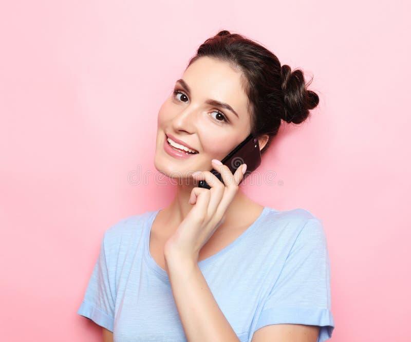 Tonårs- flicka som talar på en mobiltelefon över rosa bakgrund royaltyfri fotografi