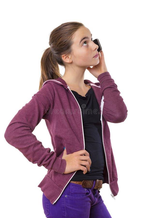 Tonårs- flicka som talar på mobiltelefonen som ser in i himlen, iso arkivbilder