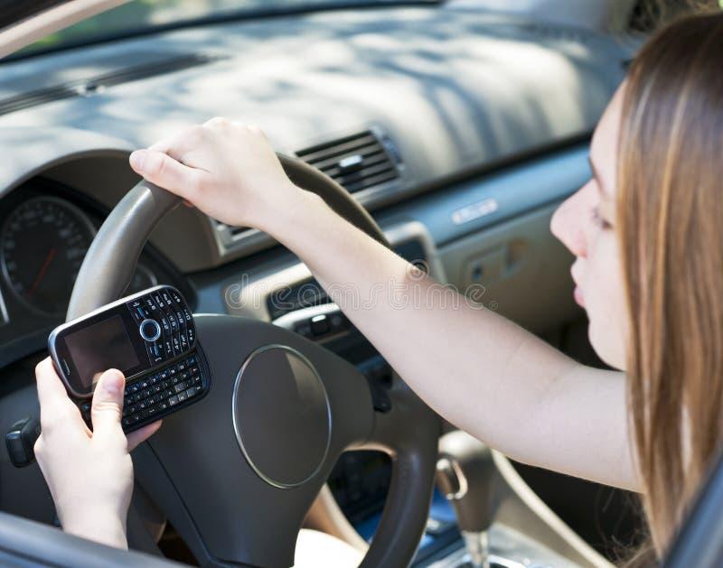 Tonårs- flicka som texting och kör arkivfoto