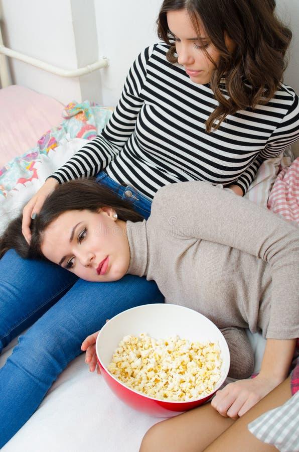 Tonårs- flicka som tröstar den ledsna flickvännen, medan hon ligger på säng fotografering för bildbyråer