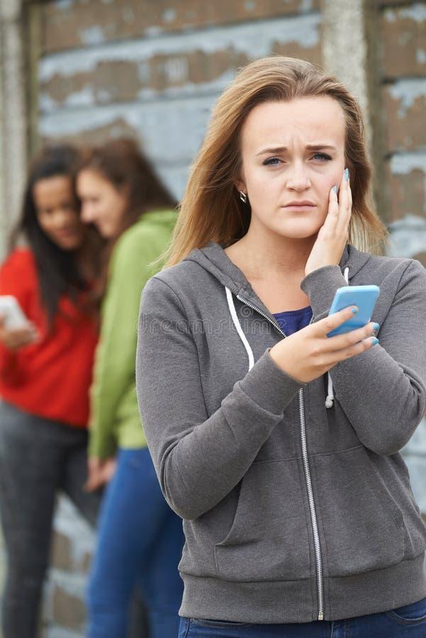 Tonårs- flicka som trakasseras av textmeddelandet arkivfoto