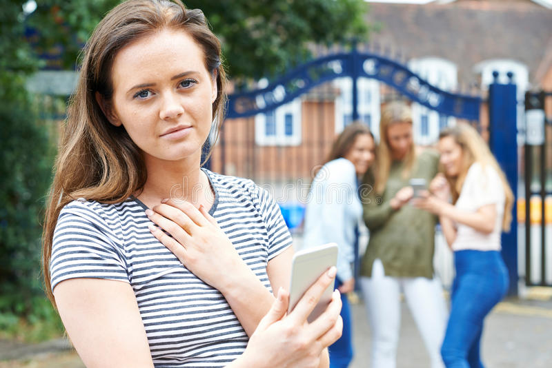Tonårs- flicka som trakasseras av textmeddelandet arkivbild