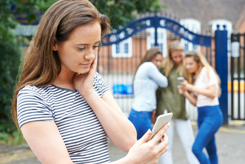 Tonårs- flicka som trakasseras av textmeddelandet arkivfoton