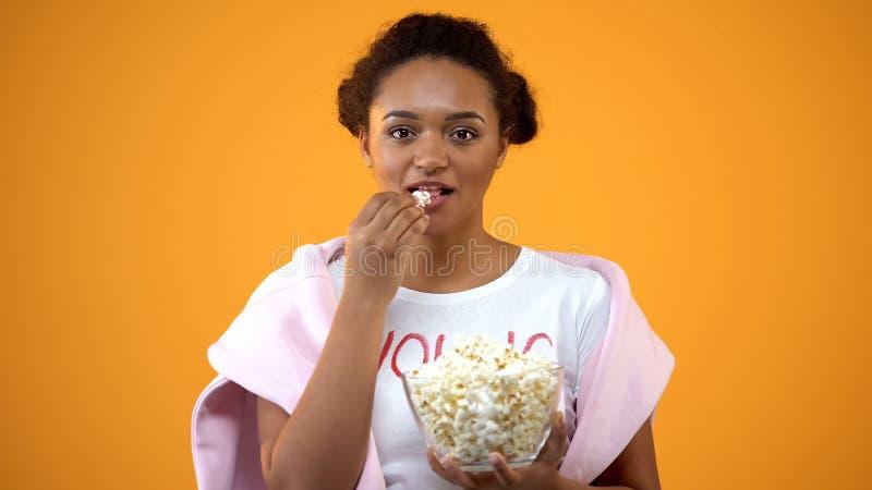 Tonårs- flicka som tycker om komediserie på tv som äter popcorn på orange bakgrund royaltyfria foton
