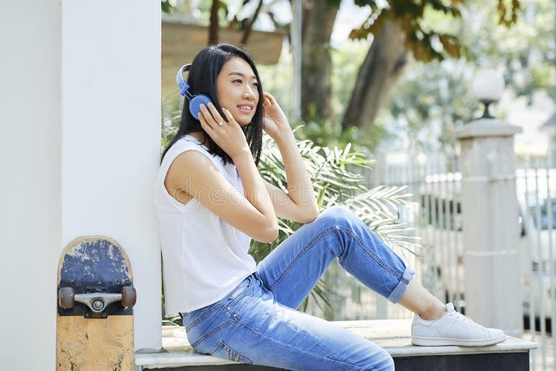 Tonårs- flicka som tycker om musik i hörlurar royaltyfri fotografi
