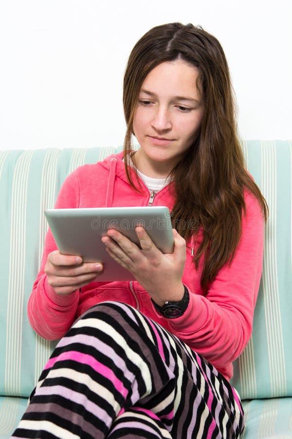 Tonårs- flickaarbete för brunett på en bordläggaPC royaltyfri fotografi