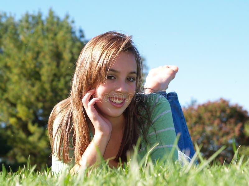 tonårs- flickagräsläggande arkivfoto