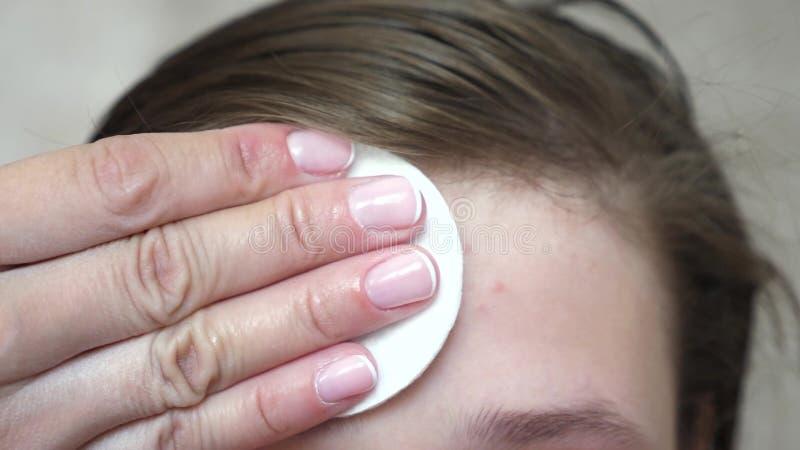 Tonårs- flickor applicerar en fuktaframsidakräm för akne Flickan gnider hennes panna med en servett Kosmetiska tillvägagångssätt  royaltyfria foton
