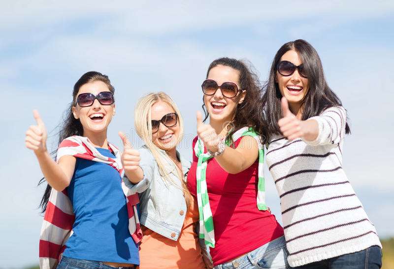 Tonårs- flickor eller unga kvinnor som visar upp tummar royaltyfri foto