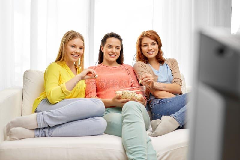 Tonårs- flickor eller vänner som hemma håller ögonen på tv royaltyfri fotografi