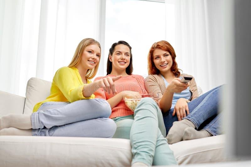 Tonårs- flickor eller vänner som hemma håller ögonen på tv arkivbilder
