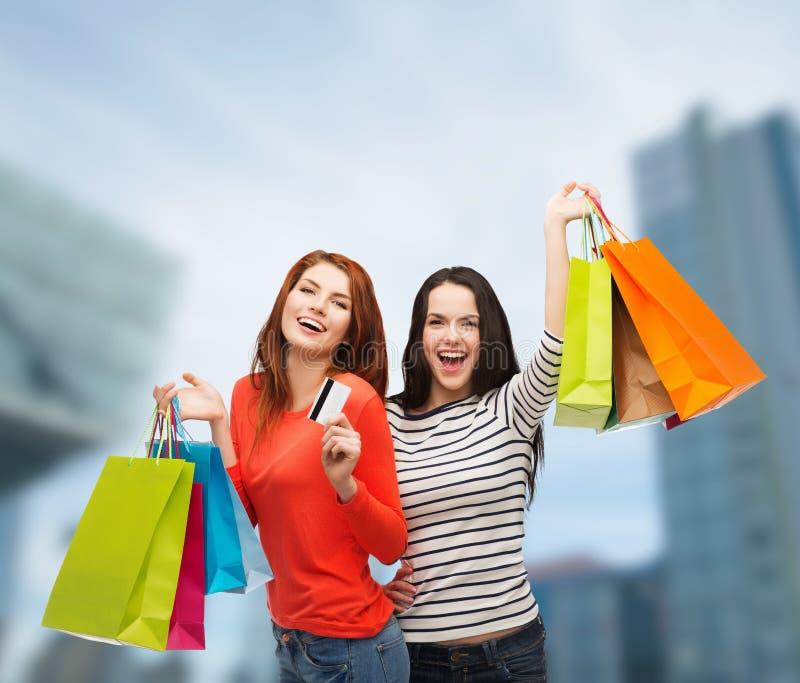 Tonårs- flickor med den shoppingpåsar och kreditkorten royaltyfri foto