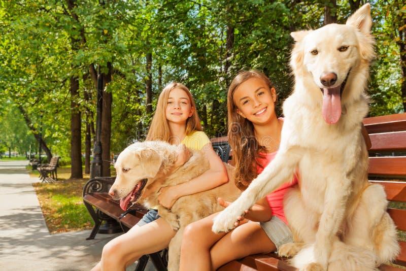 Tonårs- flickor med deras hundkapplöpning på parkerabänken arkivbilder
