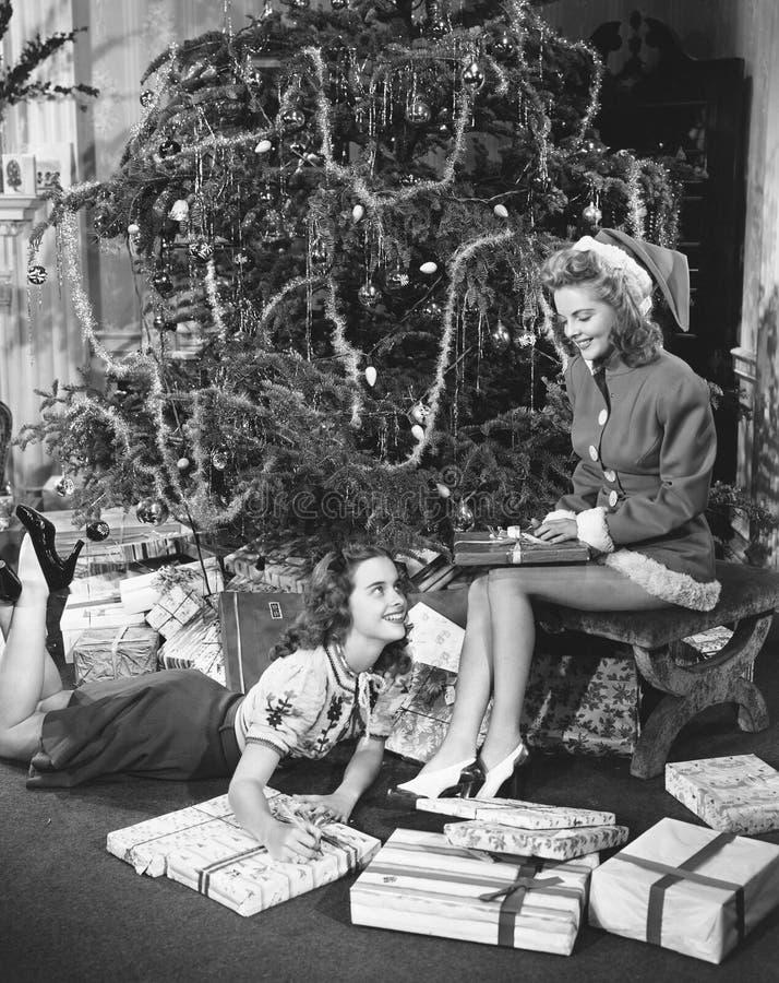Tonårs- flickor med gåvor och julgranen (alla visade personer inte är längre uppehälle, och inget gods finns Leverantörberättigan arkivfoto
