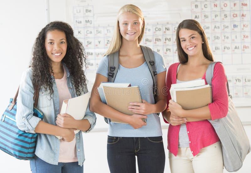 Tonårs- flickor med ryggsäckar och böcker i kemigrupp arkivbild