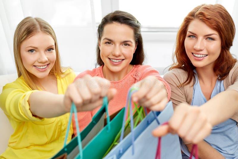Tonårs- flickor med shoppingpåsar hemma arkivfoton