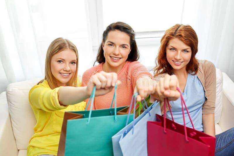 Tonårs- flickor med shoppingpåsar hemma royaltyfri foto