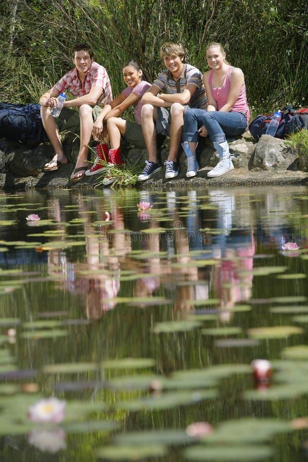 Tonårs- flickor och pojkar med ryggsäckar som sitter vid sjön royaltyfri foto