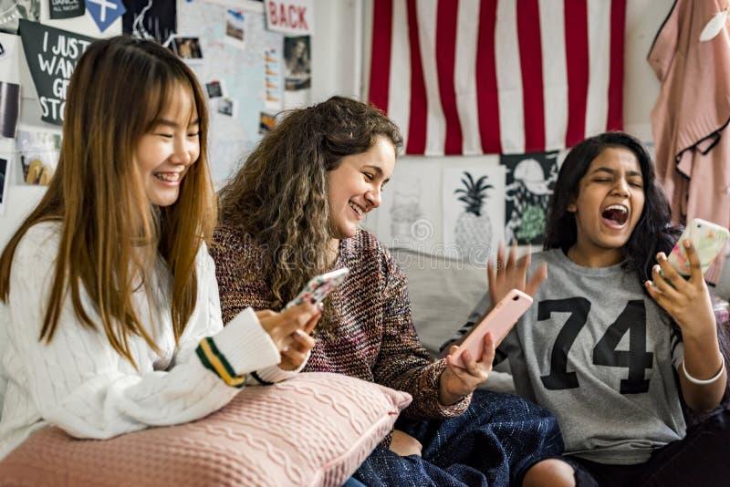Tonårs- flickor som använder smartphones i en sovruminternet i slummerparti arkivfoto