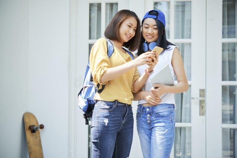 Tonårs- flickor som diskuterar den nya appen arkivbild