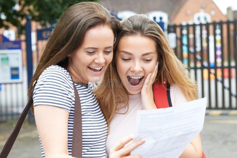 Tonårs- flickor som firar examenresultat royaltyfria bilder