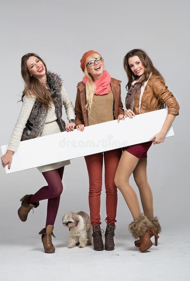 Tonårs- flickor som har gyckel med det tomma brädet royaltyfri bild