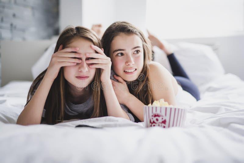 Tonårs- flickor som hemma äter popcorn och håller ögonen på fasafilm på tv royaltyfri fotografi