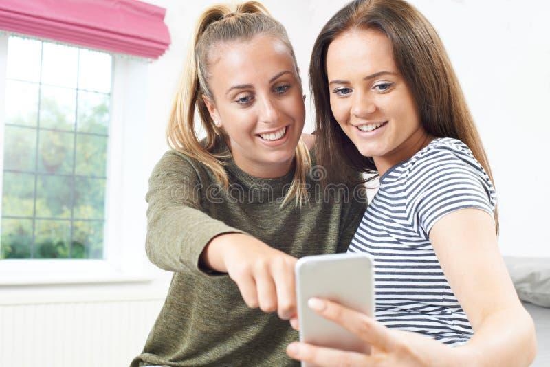 Tonårs- flickor som läser textmeddelandet på mobiltelefonen arkivfoton