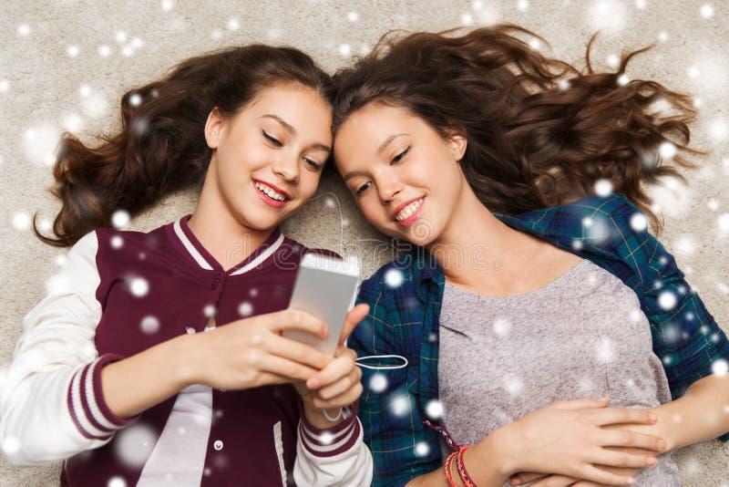 Tonårs- flickor som lyssnar till musik på smartphonen arkivbild