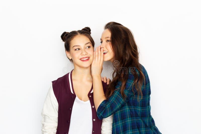 Tonårs- flickor som skvallrar eller delar hemligheter royaltyfri fotografi