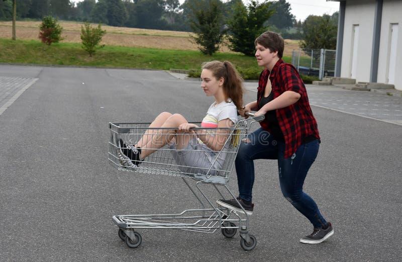Tonårs- flickvänner som har gyckel med shoppingvagnen royaltyfria bilder