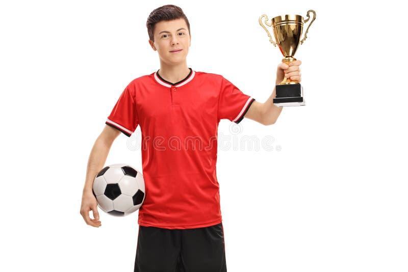 Tonårs- fotbollspelare med en fotboll och en guld- trofé royaltyfri fotografi
