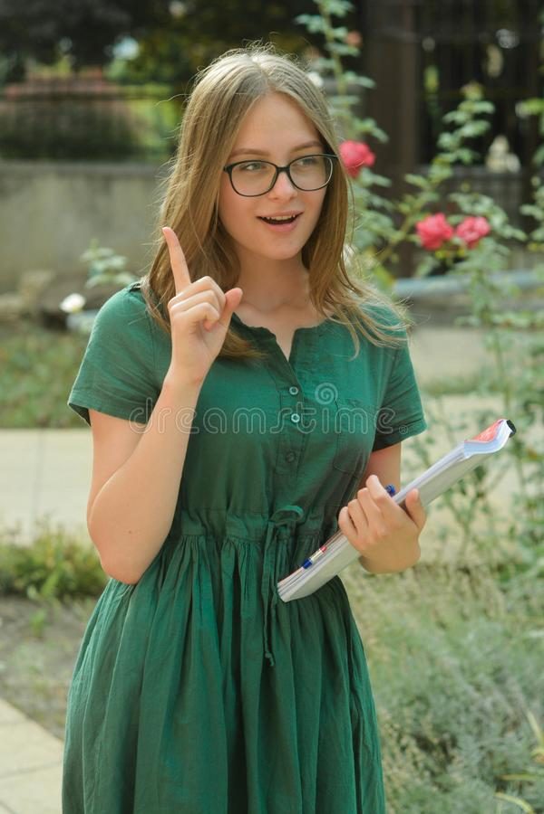 Tonårs- gullig ung flickastudent i svart glasögon som rymmer böcker Sommarferier, utbildning, begrepp - le den kvinnliga studente fotografering för bildbyråer