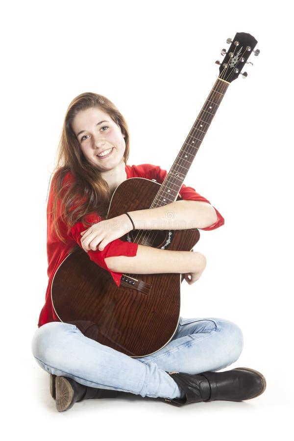 Tonårs- hållgitarr i studio royaltyfri foto