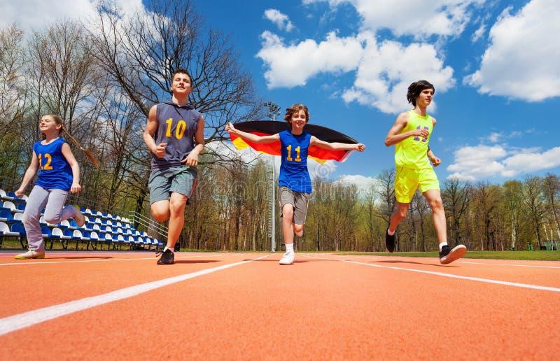 Tonårs- idrottsman nen med tysk flaggaspring på spår arkivfoton