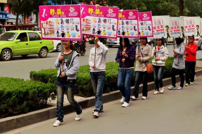 Tonårs- kinesiska flickor med advertizingplakat, Kaifeng arkivfoton