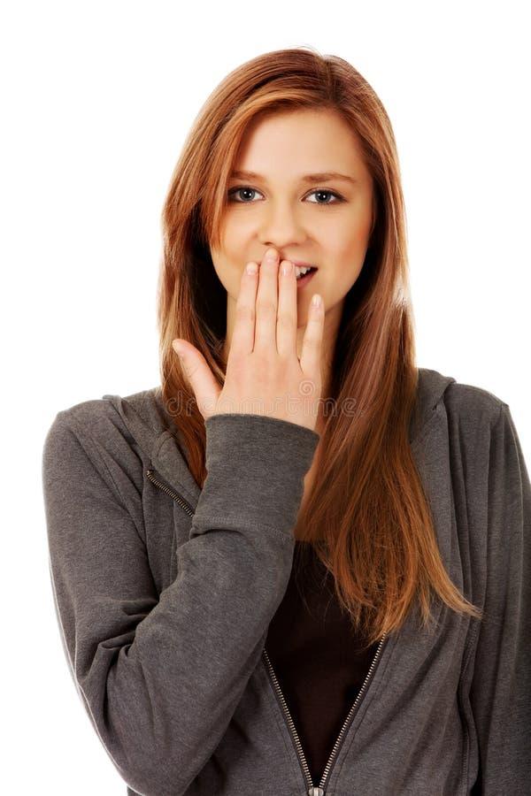 Tonårs- kvinna för fniss som täcker hennes mun med handen royaltyfri bild