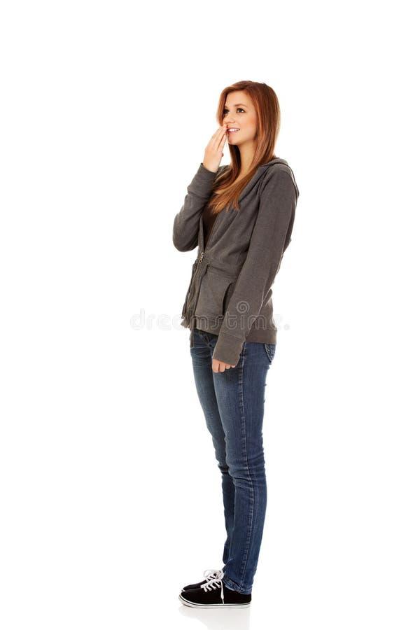 Tonårs- kvinna för fniss som täcker hennes mun med handen arkivfoton