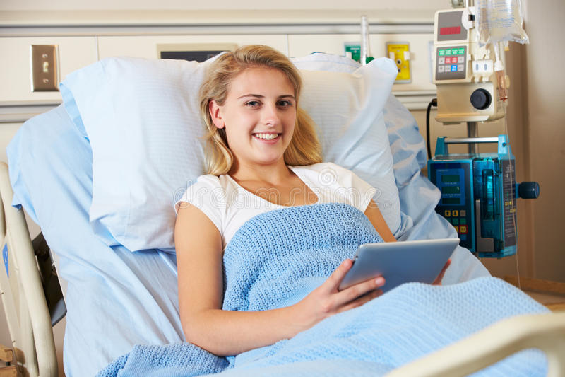 Tonårs- kvinnligt tålmodigt koppla av i sjukhussäng fotografering för bildbyråer